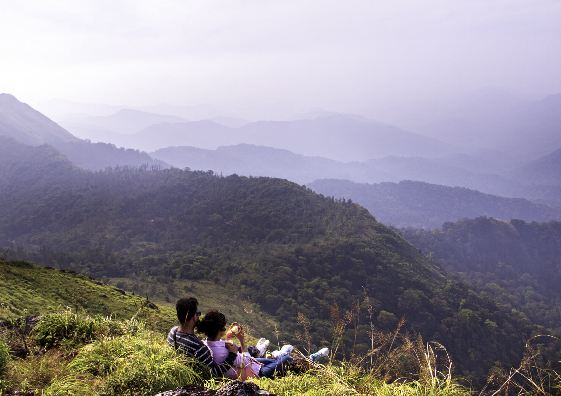 young-couple-at-top-of-a-mountain-and-enjoying-the-view-of-valley