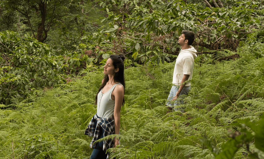 young-couple-closing-eyes-on-mountain-experiencing-nature-at-the-tamara-coorg