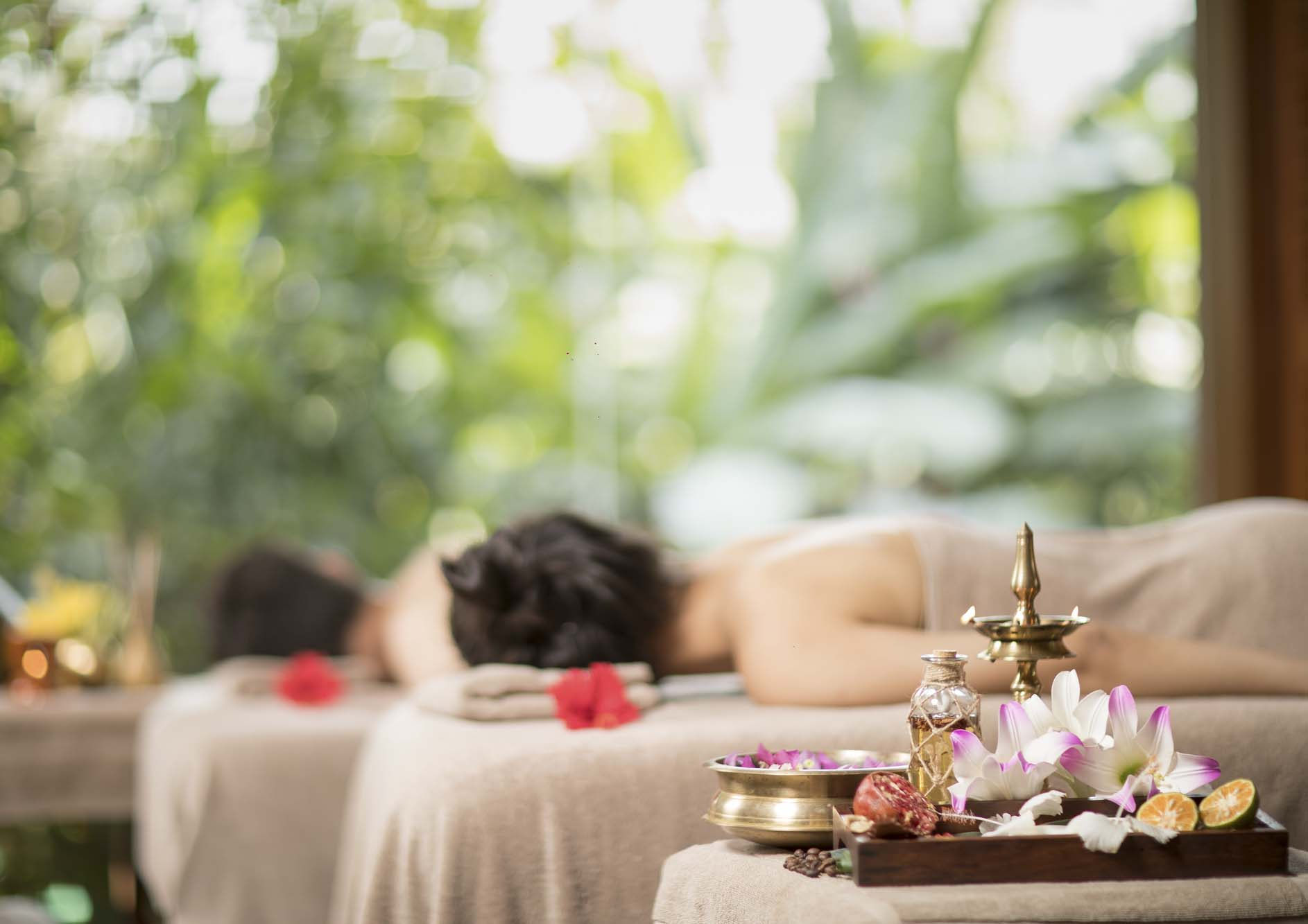 Young-man-and-woman-lying-down-on-massage-beds-at-Asian-luxury-spa-and-wellness-center